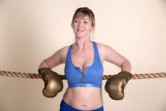 Portrait of a female boxer leaning on ropes Royalty Free Stock Image