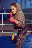 Portrait of female boxer in sport wear with fighting stance against spotlight. fitness blonde girl in sport wear. With perfect body gloved in boxing gym, posing stock image