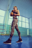 Portrait of female boxer in sport wear with fighting stance against spotlight. Sport, fitness concept. fitness blonde girl Royalty Free Stock Image