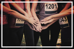Female breast cancer marathon runners stacking hands. Portrait of female breast cancer marathon runners stacking hands in park Royalty Free Stock Photography