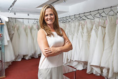 Portrait Of Female Bridal Store Owner With Wedding Dresses Stock Image