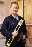Portrait Of Female Builder With Spirit Level And Electric Drill Stock Photo