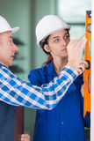 Portrait female builder with spirit level and teacher. Portrait of female builder with spirit level and her teacher royalty free stock photo