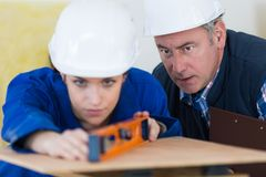 Portrait female builder with spirit level and teacher. Portrait of female builder with spirit level and teacher royalty free stock photos
