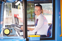 Portrait Of Female Bus Driver Behind Wheel. Sitting Down Smiling At Camera Stock Photos