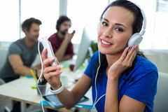 Portrait of female business executive listening to music on mobile phone Stock Photos