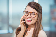 Portrait of female business executive talking on mobile phone Royalty Free Stock Image