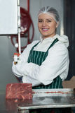 Portrait of female butcher with arms crossed standing near band saw machine Stock Photos