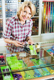 Portrait of female cashier standing at cash desk with scissors Stock Photography