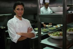 Portrait of female chef standing with arms crossed. In commercial kitchen royalty free stock photo