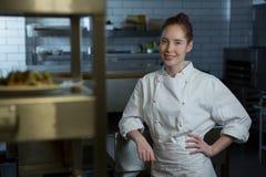 Female chef standing in the kitchen. Portrait of female chef standing in the kitchen royalty free stock photo