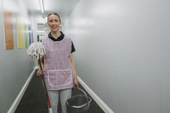 Portrait of a Female Cleaner. Portrait of a mature female cleaner with a mop and bucket in the corridor of an office building royalty free stock photography