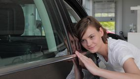 Portrait female client, Happy car service client, lucky customer. Inspecting her new automobile color, young woman customer stands next to auto, admiration from stock footage