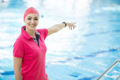 Portrait of female coach with a stop watch and clipboard by pool at leisure center royalty free stock images