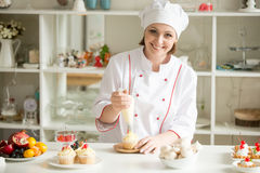 Portrait of female confectioner topping a cupcake with cream Royalty Free Stock Image