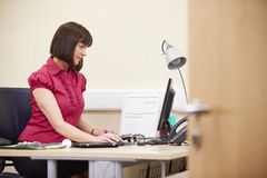 Portrait Of Female Consultant Working At Desk In Office royalty free stock photography