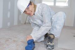 Portrait female contractor sanding floor. Portrait of female contractor sanding floor Royalty Free Stock Image