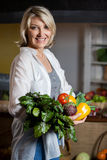 Portrait female costumer holding fresh vegetables and fruits in organic section Royalty Free Stock Image