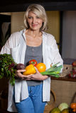 Portrait female costumer holding fresh vegetables and fruits in organic section. Of supermarket royalty free stock photography