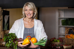 Portrait female costumer holding fresh vegetables and fruits in organic section. Of supermarket stock photography
