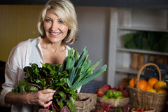 Portrait of female costumer holding fresh vegetables in organic section Royalty Free Stock Image