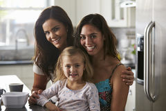 Portrait of female couple in the kitchen with their daughter Royalty Free Stock Image