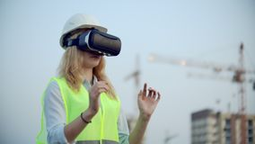 Portrait of a female crane operator operating a construction site using virtual reality glasses. Woman Construction. Portrait of a female crane operator stock video