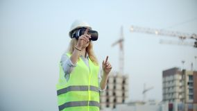Portrait of a female crane operator operating a construction site using virtual reality glasses. Woman Construction. Manager manages the progress and plan of stock video