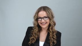 Portrait of female very rejoice and looking at camera at grey background, slow motion. Portrait of female with curly hair in bussines suit, glasses very rejoice stock footage