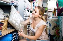 Portrait of  female customer choosing pillow in bedding section Stock Photos