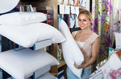 Portrait of  female customer choosing pillow in bedding section Royalty Free Stock Photography