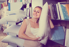 Portrait of  female customer choosing pillow in bedding section Stock Image