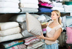 Portrait of  female customer choosing pillow in bedding section. Portrait of young female customer choosing pillow in bedding section in shop Royalty Free Stock Images