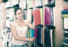 Portrait of female customer choosing tablecloths in home textile Royalty Free Stock Photography