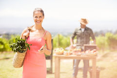 Portrait of female customer standing in front of vegetable stall Royalty Free Stock Photography