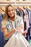 Portrait Of Female Customer Standing By Racks Of Clothes In Independent Fashion Store Holding Bags royalty free stock image
