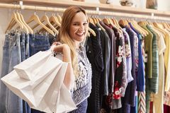 Portrait Of Female Customer Standing By Racks Of Clothes In Independent Fashion Store Holding Bags stock photography