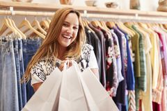 Portrait Of Female Customer Standing By Racks Of Clothes In Independent Fashion Store Holding Bags stock photo