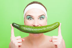 Portrait of female at dayspa. Covering her mouth with a big cucumber isolated on green background stock images
