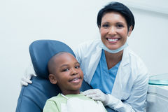 Portrait of female dentist examining boys teeth Stock Image