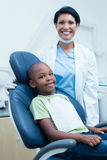 Portrait of female dentist examining boys teeth Stock Images