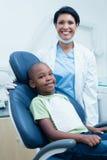 Portrait of female dentist examining boys teeth Stock Images
