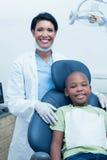 Portrait of female dentist examining boys teeth Stock Image
