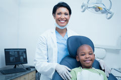 Portrait of female dentist examining boys teeth Stock Photo
