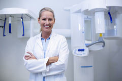 Portrait of female dentist smiling with arms crossed Stock Photos