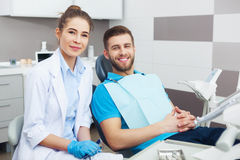 Portrait of a female dentist and young man in a dentist office. Royalty Free Stock Images