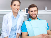 Portrait of a female dentist and young man in a dentist office. royalty free stock image