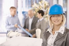 Portrait of female designer in hardhat. Smiling at camera, colleagues working in background Stock Photo