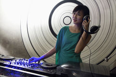 A portrait of a female DJ playing music in a nightclub Stock Image