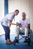 Portrait of female doctor assisting senior man in lifting dumbbell. Portrait of female doctor assisting senior men in lifting dumbbell at home Royalty Free Stock Photos